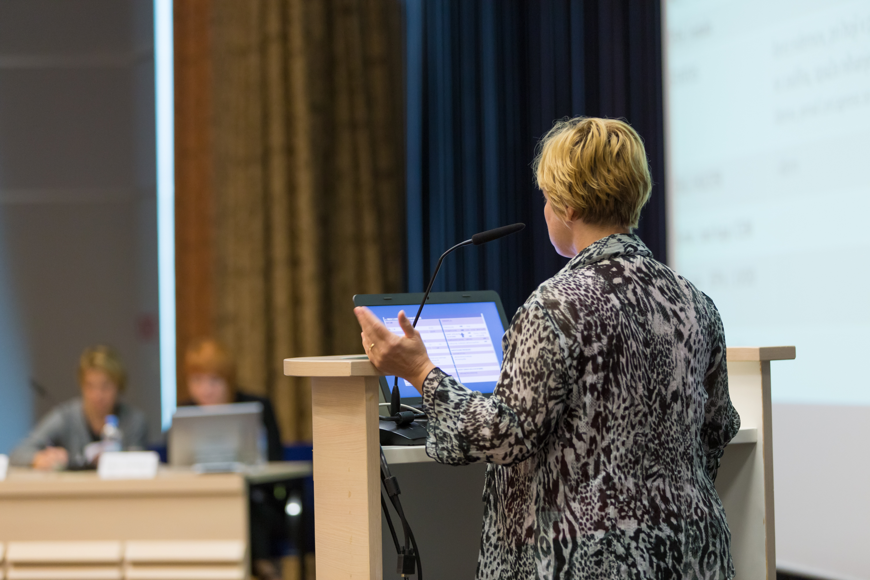 Blond female speaker presents at a scientific conference